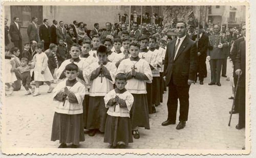Corpus-Christi procession in Aranda de Duero, Burgos, Spain, circa 1956. The author is the altar boy located in the center of the first row of three. To the right of the group is his father, Don Juan Abad Barrasús, teacher and choir director. This image reflects the spirit and atmosphere of Spain about two decades after the end of the Civil War.