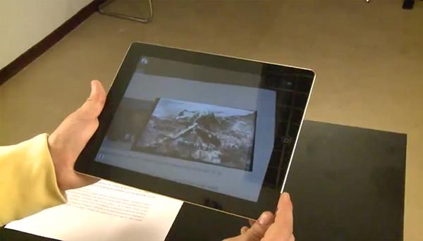 Alumno leyendo un periódico aumentado con la tableta